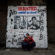 A child seats near a anti military rule graffiti in central Cairo.