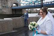 Russian bride and groom having their wedding photos taken at Tower Bridge, London, UK. It is a common site to see Russian and other nationalities having pre-wedding photographs taken at famous sites around the capital.