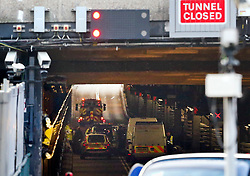 © Licensed to London News Pictures. 26/11/2015. London, UK. Police and a recovery team at the scene of the blockade in the tunnel.  A group of Airport expansion activists cause traffic chaos by blocking off the inbound tunnel of Heathrow airport in London to protest against airport expansion.  Photo credit: Peter Macdiarmid/LNP