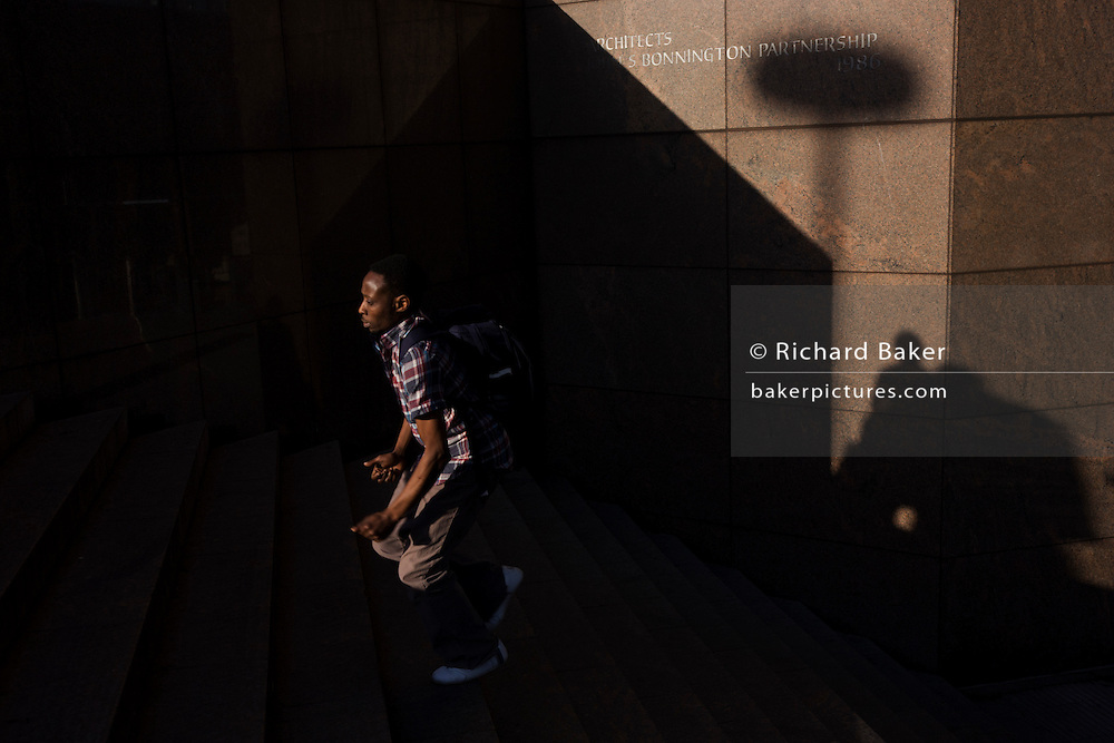 Surrounded by deep shadows, a young man climbs the steps of number 1 London Bridge.