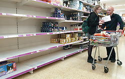 © Licensed to London News Pictures. 31/07/2021. London, UK. Shoppers stand next to nearly-empty shelves of pet food in Sainsbury's, north London. Record breaking numbers of people have been forced to self-isolate after being alerted by the NHS Covid-19 app. The pingdemic has seen staff shortages at supermarkets, resulting in less stock making its way to supermarket shelves. Labour leader Sir Keir Starmer has demanded that the government brings forward the end to self-isolation from 16 August to 7 August. Photo credit: Dinendra Haria/LNP