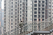 Pedestrians walk across a footbridge near new apartment constructions in Chongqing, China, on Thursday, April 14, 2016. The municipality of 30 million people saw state-led development approach fueled the fastest pace nationwide, with President Xi Jinping praising policy innovations that have included subsidized housing and relaxed residency rules that encourage labor mobility.