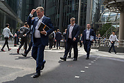 City workers cross Leadenhall in the City of London, the capitals financial district aka the Square Mile, on 10th July 2019, in London England.