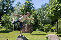 Mature woman standing on one leg on rock, Freiburg im Breisgau, Baden-Wuerttemberg, Germany