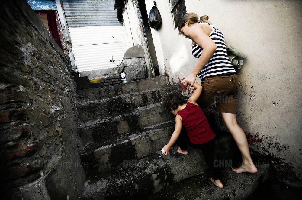 Una donna con un bambino nel cortile interno di un convettillo nel quartiere de La Boca a Buenos Aires, 4 marzo 2011.<br /> Foto Christian Mantuano / OneShot