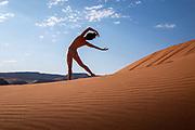 Nude woman posing in sand dunes in Moab, Utah