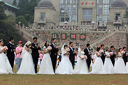 Massenhochzeit: In Wuhan heiraten 123 Hochzeitspaare / 151016 *** <br /> WUHAN, CHINA - OCTOBER 15:<br /> 123 couples participate in a group wedding ceremony on a playground near Science Building at Wuhan University on October 15, 2016 in Wuhan, Hubei Province of China. The 123 couples graduated from Wuhan university hold a group wedding in presence of their headmaster Li Xiaohong to celebrate the 123rd anniversary of Wuhan University.<br /> ©Exclusivepix Media