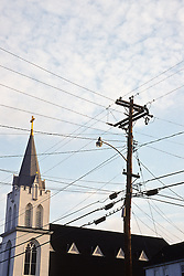 Numerous telephone and electric wires against the sky near a church