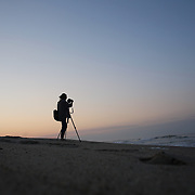 A female photographer photographs sunrise on Cisco Beach, Nantucket, Nantucket Island, Massachusetts, USA. Photo Tim Clayton