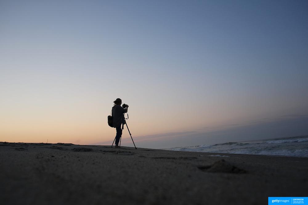 A female photographer photographs sunrise on Cisco Beach, Nantucket, Nantucket Island, Massachusetts, USA. Photo Tim Clayton