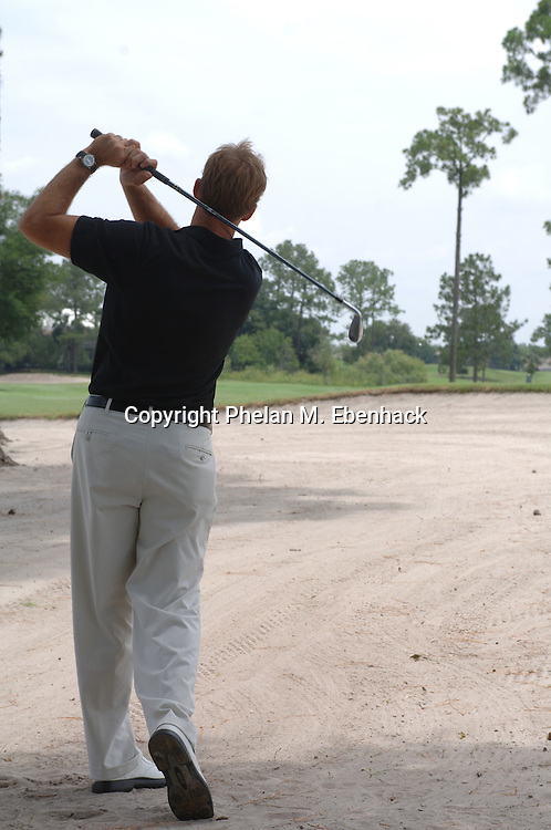 A golfer hits a ball out of the fairway bunker at a golf course near Orlando, Florida.