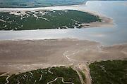 Nederland, Zeeland, Zeeuws-Vlaanderen, 12-06-2009; het Verdronken Land van Saeftinghe gezien naar het vaste land van Zeeuws-Vlaanderen, met langs de kust het Speelmansgat en de IJskelder (midden en voorgrond). Het getijdengebied op de grens met Belgie is onderdeel van het estuarium van de Schelde onder invloed van het getij zijn de kenmerkende geulen, slikken en schorren ontstaan. De voormalige polder is het grootste brakwatergebied van Europa. Het Verdronken Land is een natuurreservaat, niet vrij toegankelijk en in beheer bij het Zeeuws Landschap. Belangrijk als broed-, overwinterings- en rustgebied voor vogels.  .The Drowned Land of Saeftinghe, tidal area in the east of Dutch Flanders on the border with Belgium. The former polder is the largest brackish water of Europe and because of the the tides, there are mud flats and gullies. The Drowned Land is a nature reserve, not freely accessible. It is managed by the Zeeuws Landscape and important as bird sanctuary, part of the Scheldt estuary.Swart collectie, luchtfoto (25 procent toeslag); Swart Collection, aerial photo (additional fee required).foto Siebe Swart / photo Siebe Swart