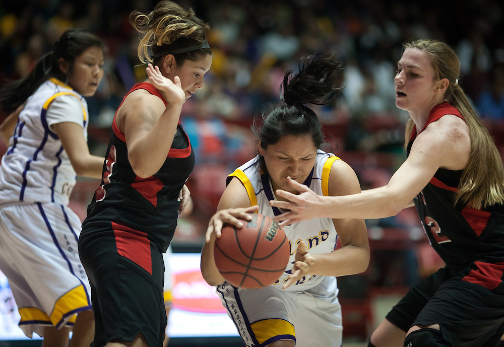 Kirtland Central's Meghan Yazzie fights for the ball against Grants Sydney Carpenter and Teige Zeller. Kirtland Central defeated Grants 53-49 in the AAAA semifinals Thursday afternoon in Albuquerque at The Pit.