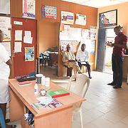 INDIVIDUAL(S) PHOTOGRAPHED: From left to right: Adetona Olubunmi, Hon Wale Ogundim, Somto and unknown. LOCATION: Ikeja Primary Health Care Center, Lagos, Nigeria. CAPTION: In the main room of the Ikeja Health Center, Somto and Hon Wale speak with the medical team.