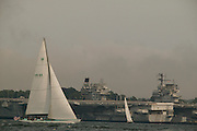 Newport, RI - 12 meter yacht intrepid sails past mothballed aircraft carriers and the newport Naval base,