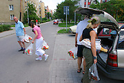 (MODEL RELEASED IMAGE). The three Sobczynscy unload the weeks' worth of groceries they just purchased at a nearby Auchan hypermarket with the help of Marzena's father Jan. (Supporting image from the project Hungry Planet: What the World Eats.) The Sobczynscy family of Konstancin-Jeziorna, Poland, is one of the thirty families featured, with a weeks' worth of food, in the book Hungry Planet: What the World Eats.