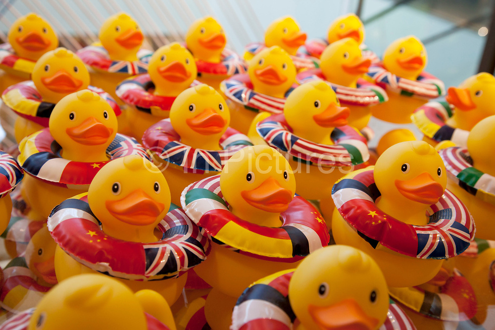 Rubber ducks for sale at a shop in London, UK. Each duck is wearing it's own rubber ring emblazoned with flags from the World.