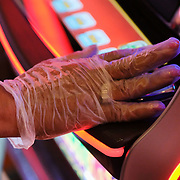A woman wears a glove while playing a slot game at the Hollywood Casino in Toledo on Wednesday, July 8, 2020. THE BLADE/KURT STEISS