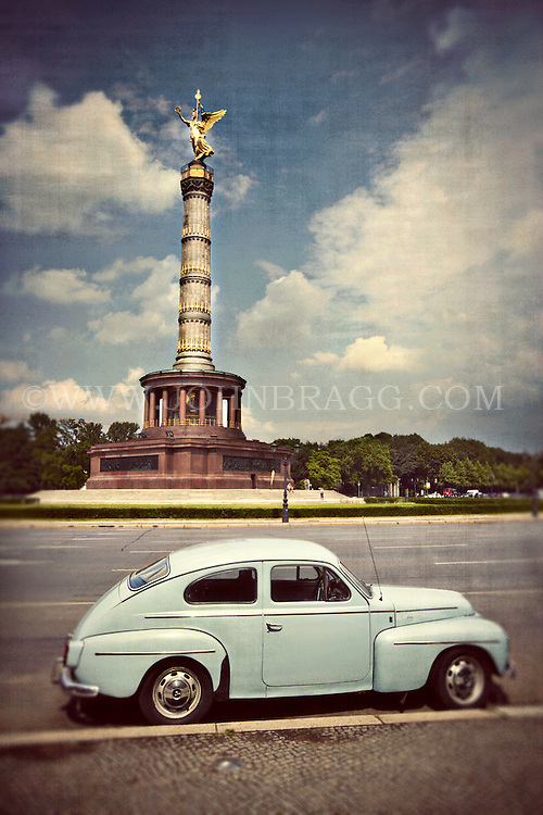 Vintage light blue Volvo parked outside the Berlin Victory Column in Berlin, Germany.