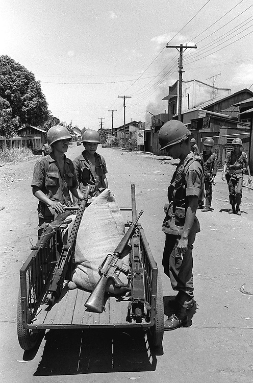 South Vietnamese troops looking at captured North Vietnamese weapons in the beseiged town of Xuan Loc, Vietnam shortly before it was captured by the North. Photographed by Terry Fincher. April 1975.