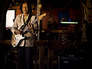An elderly african-american woman plays the blues on her electric guitar inside a bar in Atlanta.