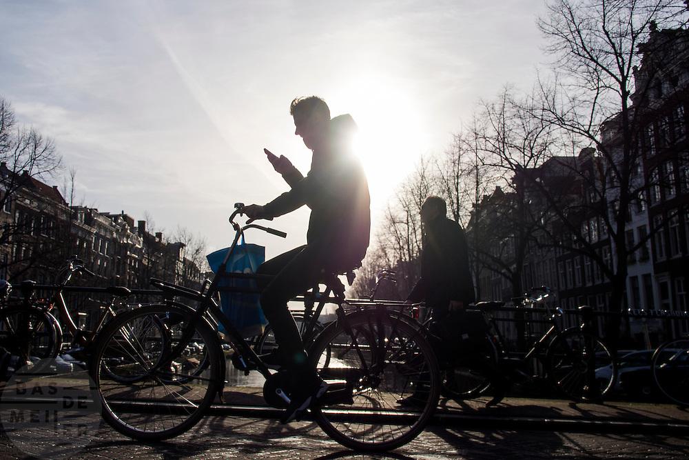 In Amsterdam fietst een man al kijkend op zijn telefoon over een brug over de Keizersgracht.<br /> <br /> In Amsterdam a man is riding his bike on a bridge over the canals while looking at his phone.