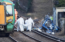 © Licensed to London News Pictures. 17/02/2018. Horsham, UK. A body is removed from the track as the remains of a car (R) is seen near a level crossing after two people were killed near the village of Barns Green after a car was hit by a train. Photo credit: Peter Macdiarmid/LNP
