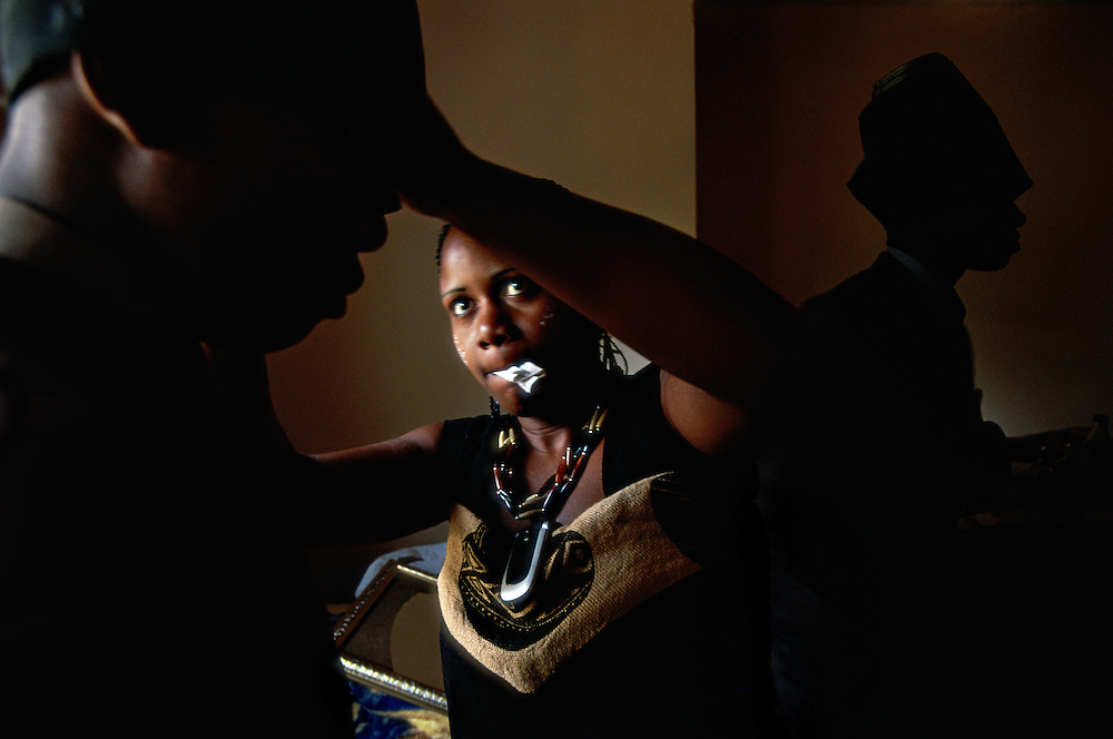 A young Xhosa woman helps a male relative, who has just returned home after one month in seclusion in an initiation camp, to adjust his turban. December 2006 in Khayalethu South Township, Knysna, South Africa. The young man, and his cousin seen in the background, have been circumcised and initiated into manhood. Following local tradition, they will wear red facial paint, a turban, long trousers, a shirt and a jacket for one week after returning home. Then they will change the turban into a cap.