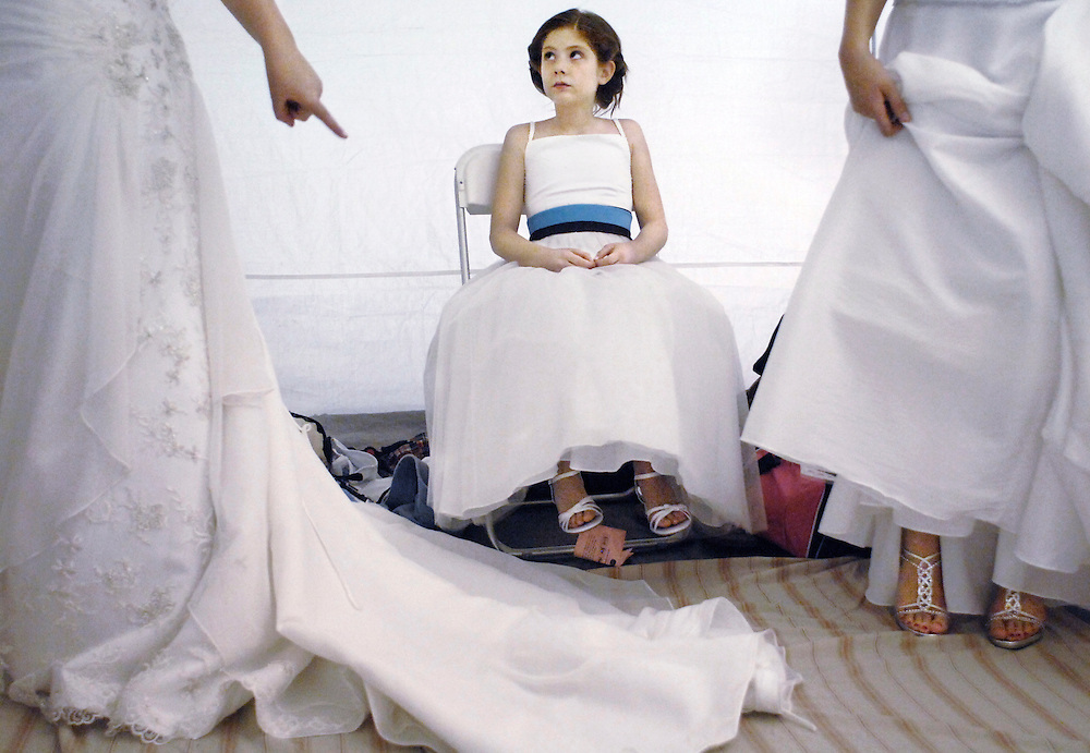 Tammy Huntsperger, left, warns daughter Hannah, 9, center, to avoid stepping on her train as she waits backstage at a wedding fashion show at the Boone County Fairgrounds.  Over 20 models, including the Huntspergers, spent the afternoon changing in and out of gowns at a frantic pace.