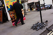 A movie industry 'standee' (a display board placed in cinema foyers) is carried past pigeons through London's Soho after use. An employee of the company that produces these boards carries one of his creations to a waiting van in a side street. But as he passes the flock of birds who are gathering under a street sign where crumbs have been dropped, we also see in the distance a poster on the side of a taxi cab which has a picture of a woman peering through a pair of binoculars, an urban bird spotter.