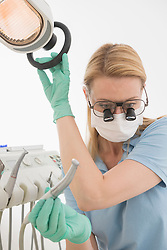 Close-up of female dentist holding dental drill with magnifiers on eyeglasses, Munich, Bavaria, Germany