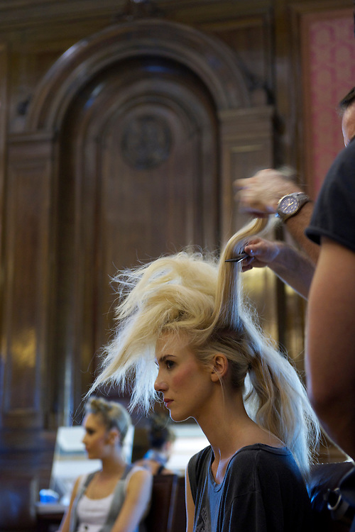 Models are made up by stylists backstage at a contour design fashion show in Freemasons' Hall, London..