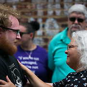 CHARLOTTESVILLE, VA - AUGUST 12,  2018: Susan Bro, mother of Heather Heyer, comforts a person at the spot where her daughter was killed exactly one year ago. Bro spoke and met with friends. family and mourners. Logan Cyrus/AFP