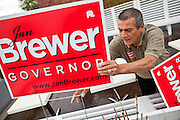 24 AUGUST 2010 -- TUCSON, AZ: Paul Mondello (CQ) a supporter of Gov Brewer sets out signs for the gov before her appearance in Tucson Tuesday night. Gov Brewer made an appearance at Mr. An's Teppan Steak & Sushi in Tucson Tuesday night just as early returns in Arizona's primary elections were starting to come in. Brewer's victory has been credited to her signing SB 1070 and taking a tough stand on illegal immigration and against the Obama administration.    PHOTO BY JACK KURTZ
