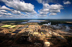 CANADA ALBERTA FORT MCMURRAY 20JUL09 - Aerial view of Syncrude upgrader in the Boreal forest north of Fort McMurray, northern Alberta, Canada.<br /> <br /> The tar sand deposits lie under 141,000 square kilometres of sparsely populated boreal forest and muskeg and contain about 1.7 trillion barrels of bitumen in-place, comparable in magnitude to the world's total proven reserves of conventional petroleum. Current projections state that production will  grow from 1.2 million barrels per day (190,000 m³/d) in 2008 to 3.3 million barrels per day (520,000 m³/d) in 2020 which would place Canada among the four or five largest oil-producing countries in the world.<br /> <br /> The industry has brought wealth and an economic boom to the region but also created an environmental disaster downstream from the Athabasca river, polluting the lakes where water and fish are contaminated. The native Indian tribes of the Mikisew, Cree, Dene and other smaller First Nations are seeing their natural habitat destroyed and are largely powerless to stop or slow down the rapid expansion of the oil sands development, Canada's number one economic driver.<br /> <br /> jre/Photo by Jiri Rezac / GREENPEACE<br /> <br /> 