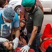 1 May 2021<br /> <br /> Indirapuram, Gazhiabad<br /> Volunteers attempt to revive a patient ( Vishal) who had passed out and had a very low pulse while his wife clings to his foot in desperation at the Indirapuram Gurudwara ( Sikh Temple). The temple has a free oxygen facility  for Covid positive patients who have not found a hospital or oxygen support . The camp under a cloth tent on the road is a makeshift setup without proper medical support. As a result when Vishals  condition worsened they had no option but to send the family to the nearest emergency ward of a hospital to try getting help. Vishal was put into the families car barely breathing.