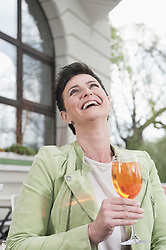 Mature woman laughing with aperol spritzat at sidewalk cafe, Bavaria, Germany