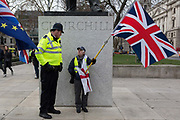 On the day that Prime Minister Theresa Mays Meaningful Brexit vote is taken in the UK Parliament, a Leave supporter is spoken to by a Met Police officer beneath the statue of Winston Churchill in Parliament Square, on 15th January 2019, in Westminster, London, England.