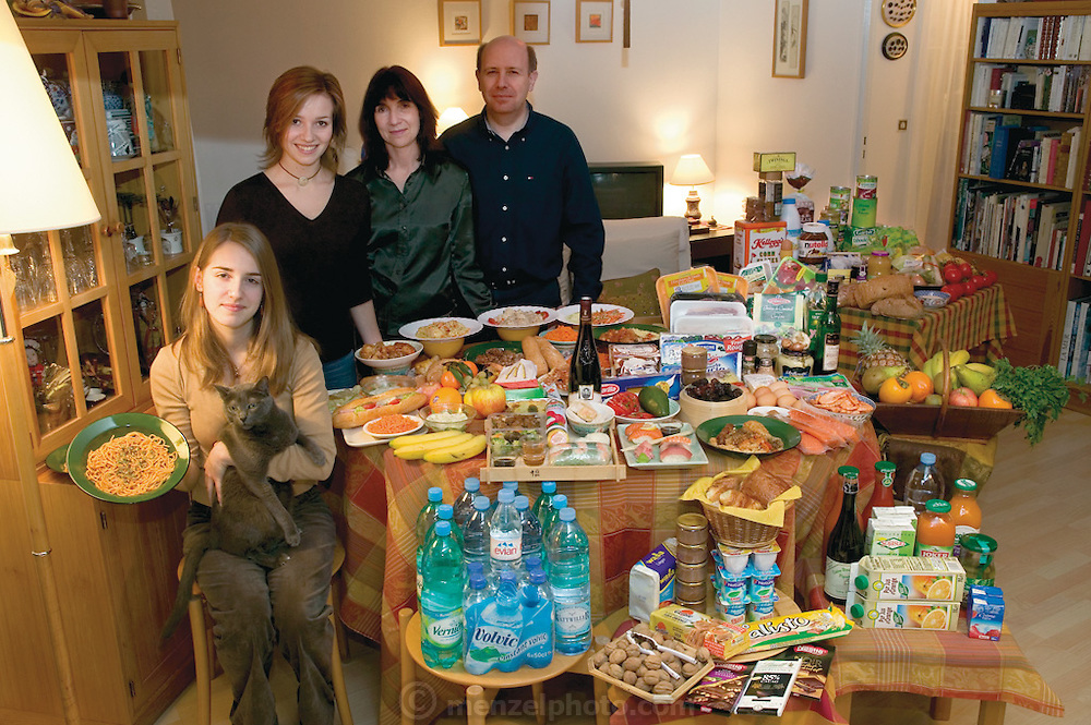 (MODEL RELEASED IMAGE). The Le Moine family in the living room of their apartment in the Paris suburb of Montreuil, with a week's worth of food. Michel Le Moine and Eve Le Moine,  stand behind their daughters, Delphine (standing), and Laetitia (holding spaghetti and Coppelius the cat). The Le Moine family is one of the thirty families featured in the book Hungry Planet: What the World Eats (p. 124).