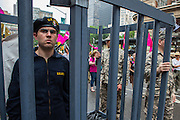 A man playing the part of Bradley Manning, a gay soldier accused in the Wikileaks case, is behind bars and guarded by men playing the parts of soldiers.