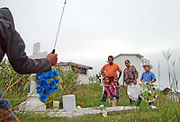 """MEXICO, Veracruz, Tantoyuca, Oct 27- Nov 4, 2009. A family waits for a worker to clear their friend's grave in Tantoyuca's main cemetery.""""Xantolo,"""" the Nahuatl word for """"Santos,"""" or holy, marks a week-long period during which the whole Huasteca region of northern Veracruz state prepares for """"Dia de los Muertos,"""" the Day of the Dead. For children on the nights of October 31st and adults on November 1st, there is costumed dancing in the streets, and a carnival atmosphere, while Mexican families also honor the yearly return of the souls of their relatives at home and in the graveyards, with flower-bedecked altars and the foods their loved ones preferred in life. Photographs for HOY by Jay Dunn."""