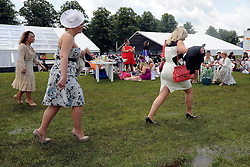 © licensed to London News Pictures. ASCOT, UK.  16/06/11. Ladies avoisd puddles in one of the enclosures. Ladies Day at Royal Ascot 16 June 2011. Royal Ascot has established itself as a national institution and the centrepiece of the British social calendar as well as being a stage for the best racehorses in the world. Mandatory Credit Stephen Simpson/LNP