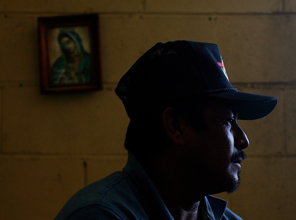 A portrait of the Virgin Mary hangs on the wall as Fidel Meza, of Hidalgo, Mexico visits a house-mate's bedroom. Meza had to return home early to Mexico because of the death of his mother.