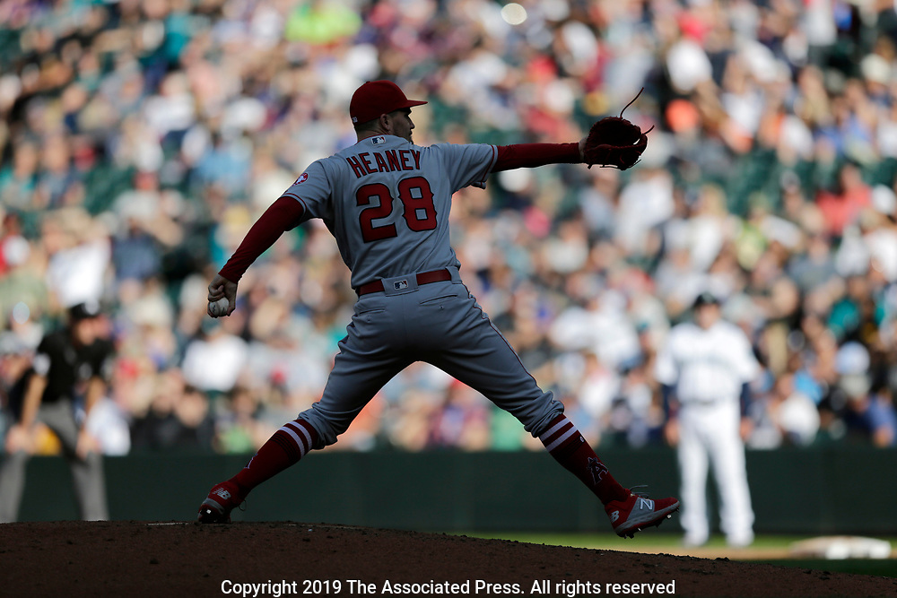 Los Angeles Angels starting pitcher Andrew Heaney works in the shadows with sun hitting fans behind against the Seattle Mariners during the first inning of a baseball game, Saturday, June 1, 2019, in Seattle. (AP Photo/John Froschauer)