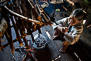 An old Bahnar ethnic woman lights a pipe and sits close to a fireplace. Pleiku, Vietnam, Asia