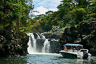 Mauiritus Island. Some people relaxing on deck of yacht. River waterfall