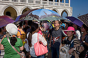 Chinese tourists with umbrellas in Piazza San Marco, Venice, Italy