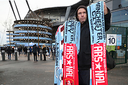 A vendor sells half and half scarves during the Premier League match at the Etihad Stadium, Manchester.