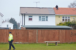 © Licensed to London News Pictures.  05/03/2013. AYLESBURY, UK. Errol Clarke (pictured on roof) attempts to avoid arrest by staging a sit-in on the roof of his own house in Russell Avenue, Aylesbury since yesterday (Tue 5th). Clarke is wanted by the police after absconding during a high court hearing in mid-December 2012. He was taken to court by the District Council for allegedly breaking an injunction preventing his land being used for a gypsy campsite. He remained on the roof for 26 hours before coming down and was promptly arrested. Photo credit :  Cliff Hide/LNP