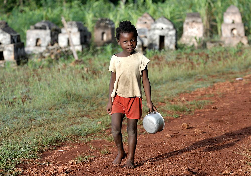 A girl walks past graves in the Haitian village of Mizak.